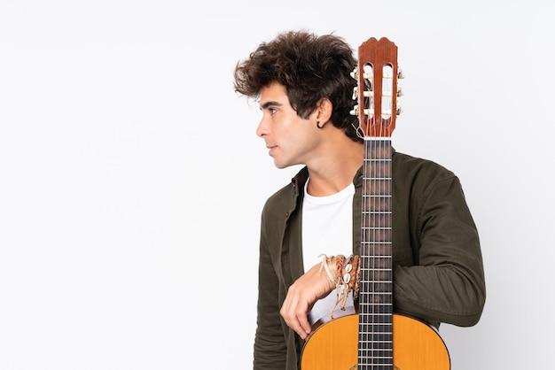 孤立した白い壁の上のギターを持つ若い白人男