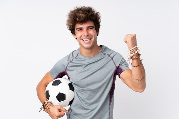 Молодой кавказский человек над изолированной белой стеной с футбольным мячом празднуя победу