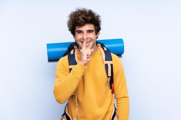 沈黙のジェスチャーをしている孤立した青い壁の上の大きなバックパックを持つ若い登山家男