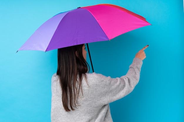 Молодая брюнетка женщина держит зонтик над синей стеной, указывая назад указательным пальцем