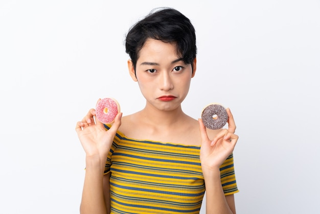 悲しい表情でドーナツを持って若いアジアの女の子