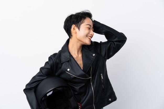 Молодая азиатская девушка с мотоциклетным шлемом над изолированной белой стеной что-то поняла и намеревается найти решение