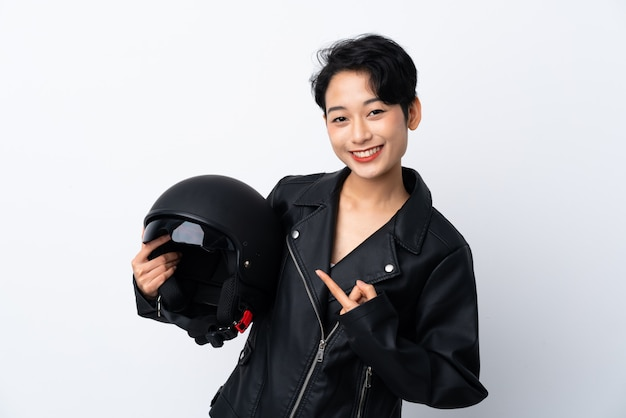 Молодая азиатская девушка с шлемом мотоцикла над изолированной белой стеной и указывать его