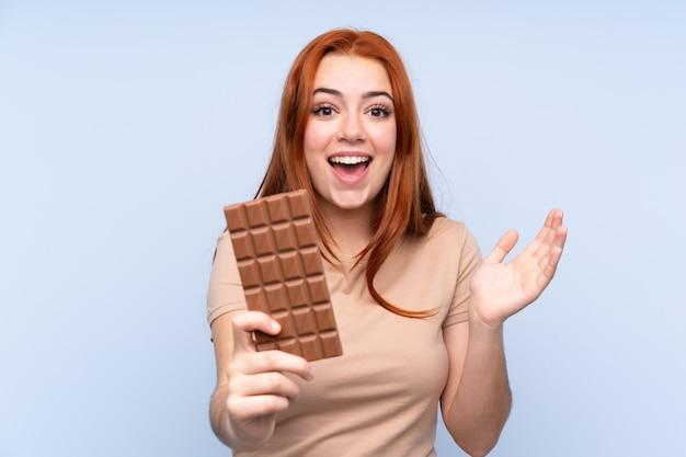 チョコレートタブレットを取って驚いた分離の青い壁の上の赤毛のティーンエイジャーの女の子