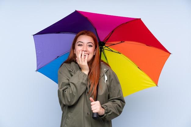 赤毛のティーンエイジャーの女の子が驚きの表情で孤立した青い壁に傘をかざす