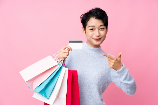ショッピングバッグとクレジットカードを保持している孤立したピンクの壁の上の若いアジアの女の子