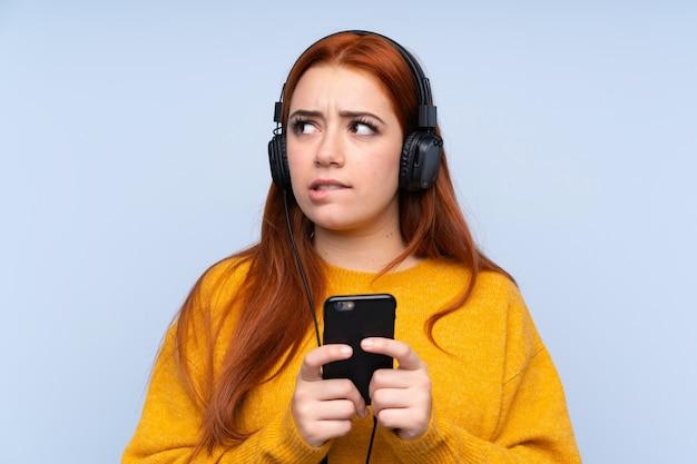 携帯電話で音楽を聴くと分離の青い壁の上の赤毛のティーンエイジャーの女の子と思考
