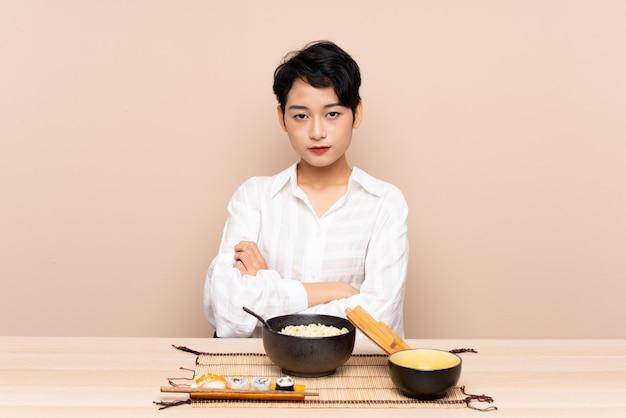 麺と寿司の腕を組んで維持するテーブルで若いアジアの女の子