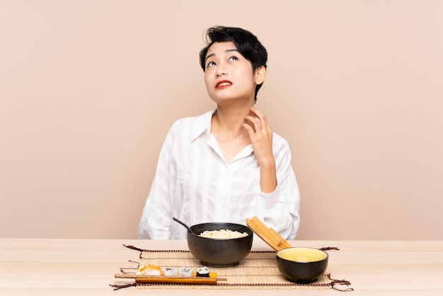 麺と寿司のアイデアを考えてのボウルとテーブルの若いアジアの女の子