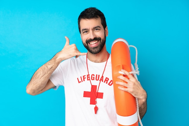 Человек спасателя над изолированной голубой стеной делая жест телефона. перезвони мне знак