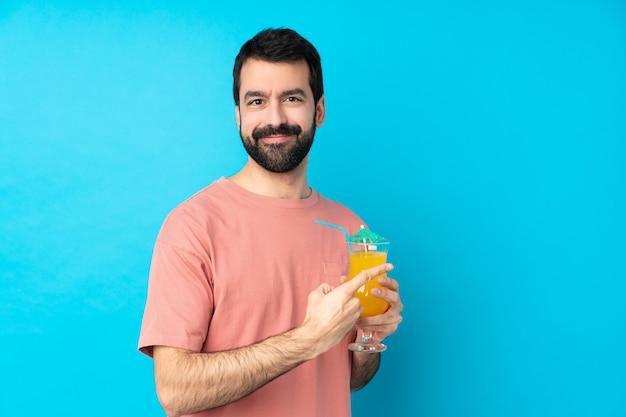 製品を提示する側を指している分離の青い壁にカクテルをかざす以上の若い男