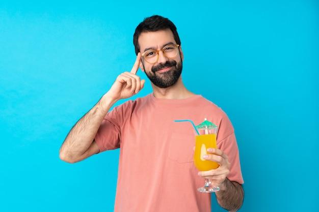 メガネで孤立した青い壁にカクテルを押しながら笑顔の若い男