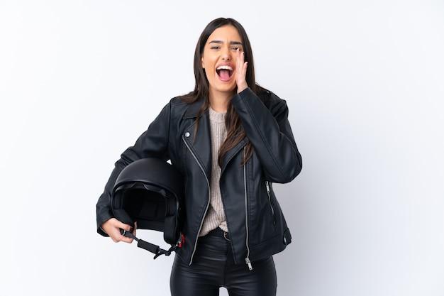 口を大きく開けて叫んで孤立した白い壁にオートバイのヘルメットを持つ若いブルネットの女性