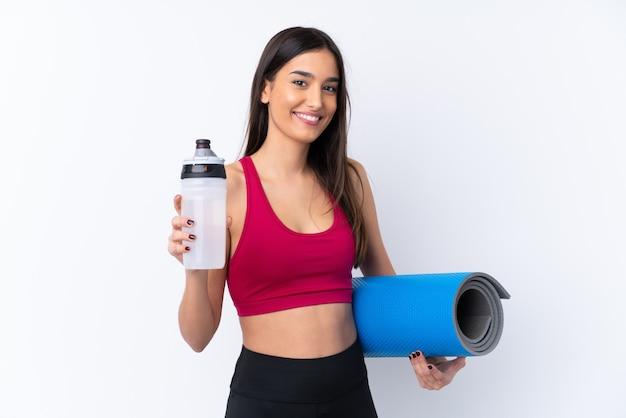 Молодая женщина брюнет спорта над изолированной белой стеной с бутылкой с водой спортов и с циновкой