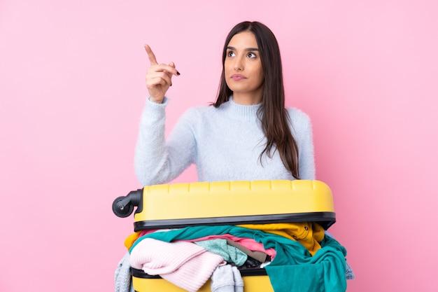 透明なスクリーンに触れる分離のピンクの壁の上の服でいっぱいのスーツケースを持つ旅行者女性