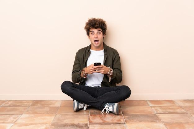 驚いたとメッセージを送信する床に座っている若い白人男