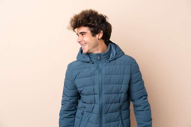 Куртка зимы человека нося над изолированной стеной смотря сторону