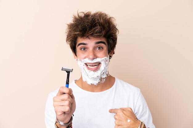 Молодой красавец брить бороду с удивленным выражением лица