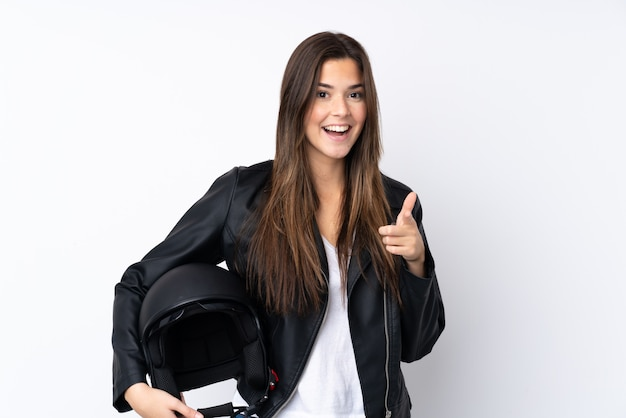 Молодая женщина с мотоциклетным шлемом над белой стеной показывает пальцем на тебя