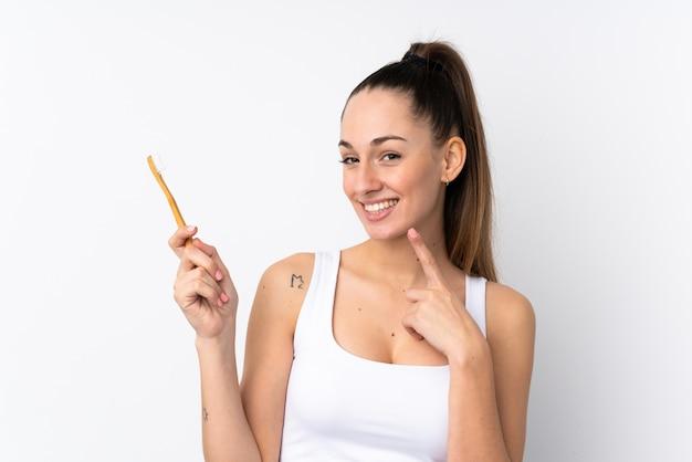 Молодая брюнетка женщина над изолированной белой стеной с зубной щеткой и счастливым выражением