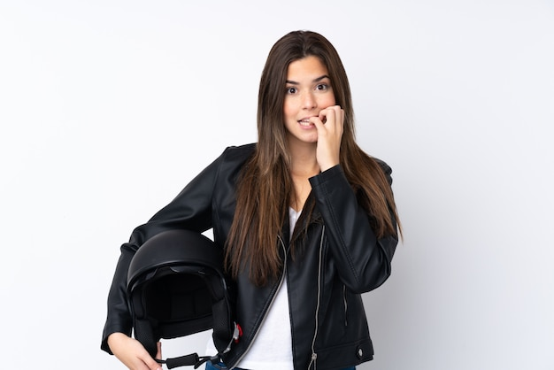 孤立した白い壁にオートバイのヘルメットを持つ若い女性神経質で怖い
