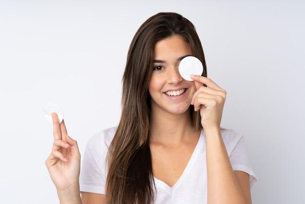 Девушка-подросток над изолированной стеной с ватным тампоном для снятия макияжа с лица и улыбки