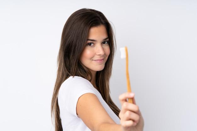 Девушка-подросток над изолированной стеной с зубной щеткой
