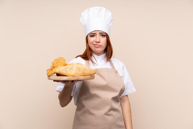 Рыжая девушка подросток в форме шеф-повара. женский пекарь держит стол с несколькими хлебов с грустным выражением