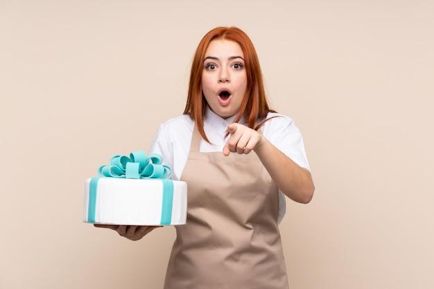孤立した壁の上の大きなケーキと赤毛のティーンエイジャーの女の子が驚いて、フロントを指す