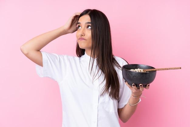 箸で麺のボウルを押しながら混乱している表情と混乱している分離のピンクの壁の上の若いブルネットの女性
