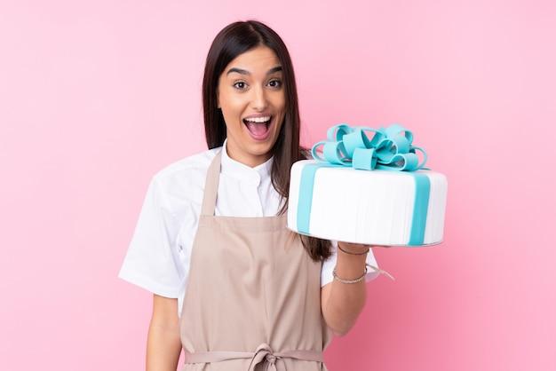 驚きとショックを受けた表情で孤立した壁の上の大きなケーキを持つ若い女性