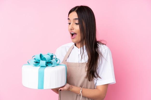 孤立した壁の上の大きなケーキを持つ若い女性