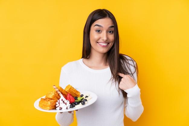 Молодая брюнетка женщина, держащая вафли над стеной с удивленным выражением лица