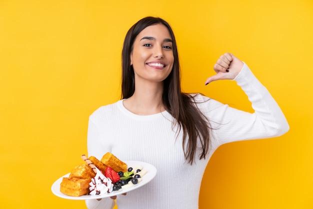Молодая брюнетка женщина, держащая вафли над изолированной стеной, гордый и самодовольный