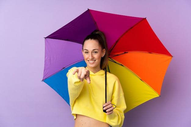 Молодая брюнетка с зонтиком на фиолетовом фоне уверенно показывает пальцем на тебя