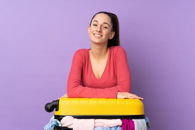孤立した紫色の壁の上の服でいっぱいのスーツケースを持つ旅行者女性