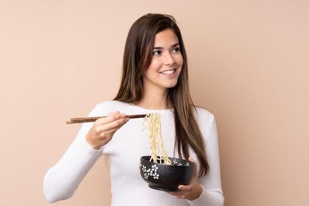 箸で麺のボウルを押しながら見上げる孤立した壁の上のティーンエイジャーの女の子