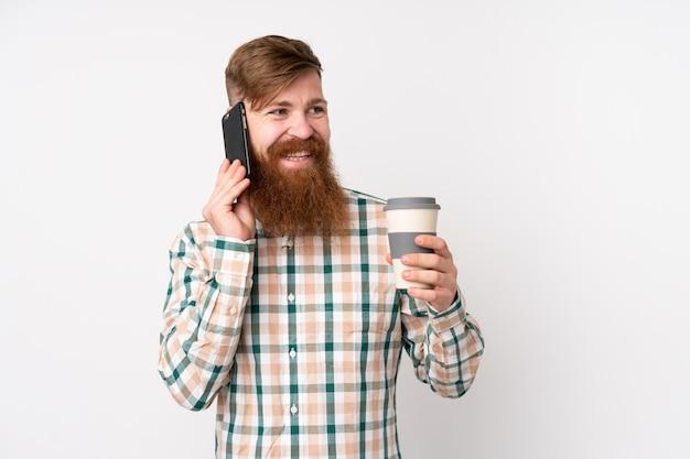 コーヒーを奪うと携帯電話を保持している孤立した白い壁の上の長いひげを持つ赤毛の男