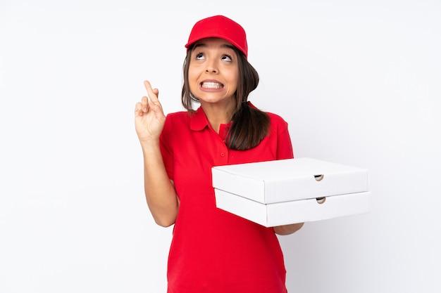 指を交差し、最高を願って孤立した白い壁に若いピザ配達の少女