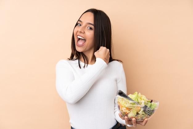 勝利を祝って孤立した壁にサラダを置く若いブルネットの少女