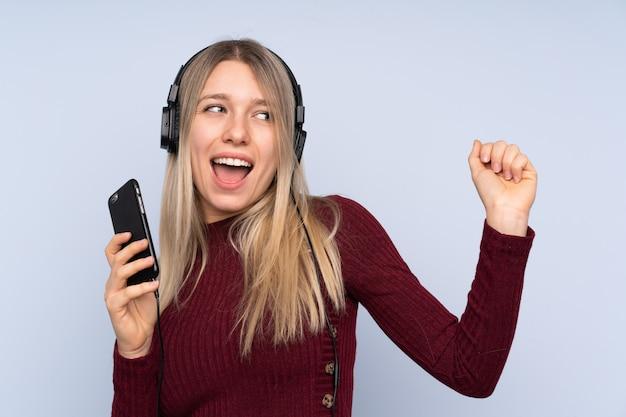 携帯電話と歌で音楽を聴く分離の青い壁の上の若いブロンドの女性