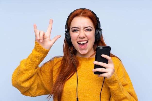 Рыжая девушка-подросток над изолированной синей стеной, слушая музыку с мобильного телефона, делая рок жест