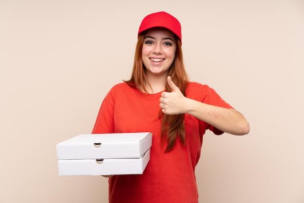 親指をあきらめて孤立した壁にピザを置くピザ配達ティーンエイジャーの女性