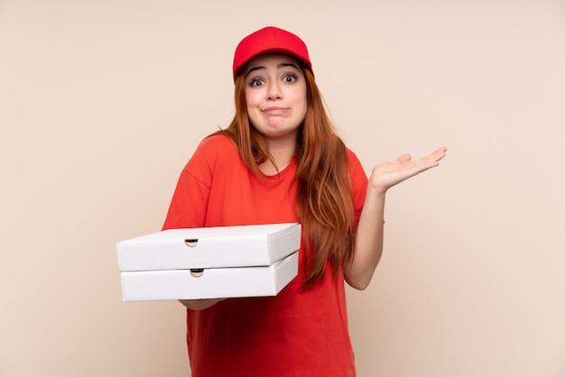 混乱した表情で疑問を持つ孤立した壁にピザを保持しているピザ配達ティーンエイジャーの女性