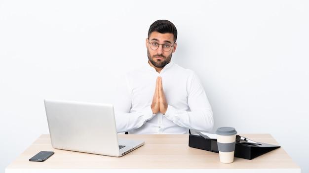 Молодой предприниматель на рабочем месте держит ладони вместе. человек просит что-то