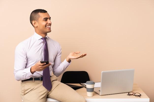 Молодой деловой человек в офисе, протягивая руки в сторону за приглашение прийти