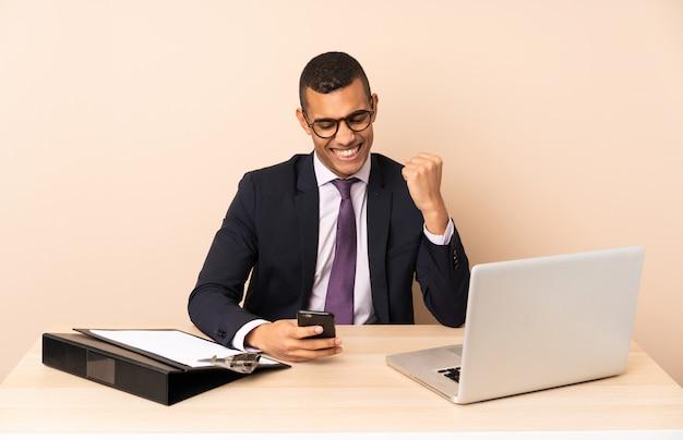Молодой деловой человек в своем кабинете с ноутбуком и другие документы с телефоном в победной позиции