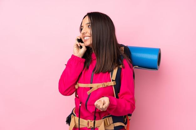 Молодая альпинистка с большим рюкзаком над изолированной розовой стеной ведет с кем-то разговор по мобильному телефону