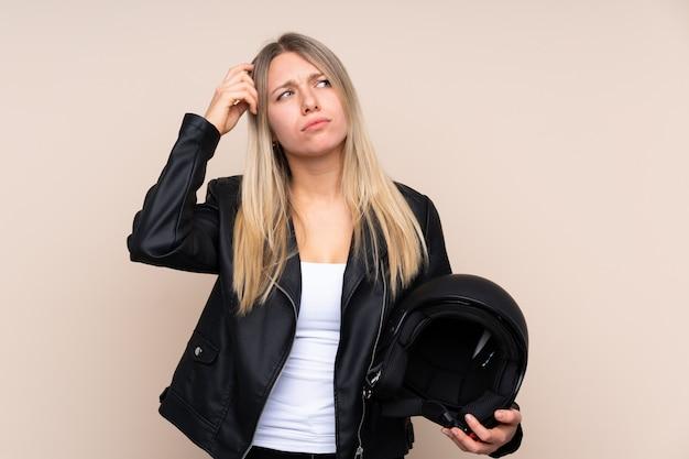 疑問を持っている孤立した壁の上のオートバイのヘルメットと混乱の表情を持つ若いブロンドの女性