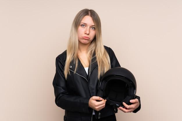 悲しい孤立した壁の上のオートバイのヘルメットを持つ若いブロンドの女性
